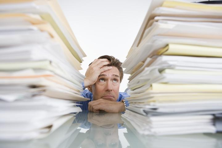 書類の山に頭を抱える人