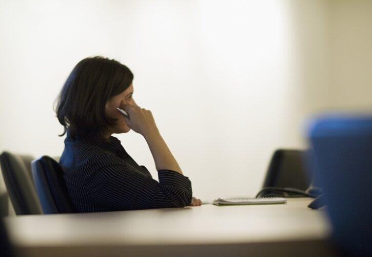 デスクで考え事をする女性