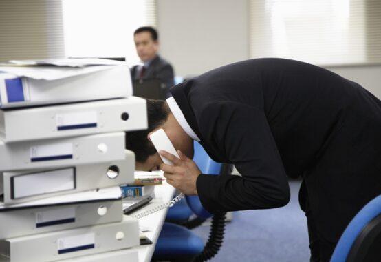 電話をかけながら頭を下げている男性