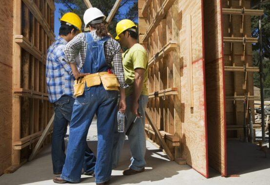 建築現場で相談する3人の作業員