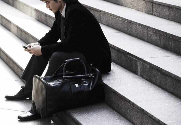 街中の会談で座ってしんみりしているスーツの男性