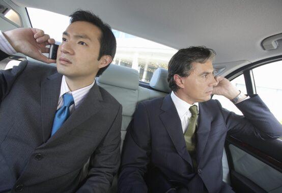 自動車の中でお互いそっぽを向く二人の男性