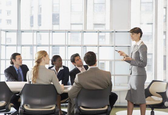 会議室でメンバーに説明する女性