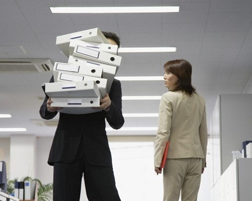 前が見えないほど大量の書類を運ぶ男性
