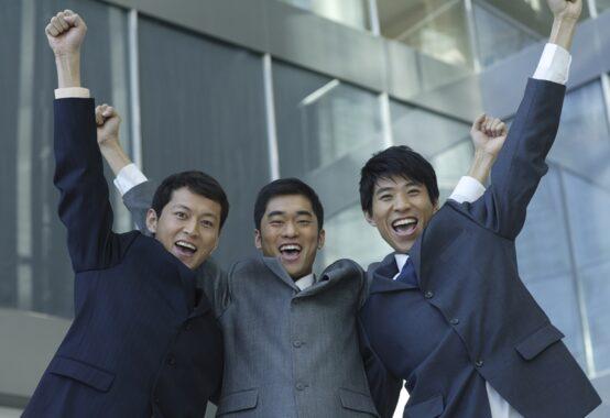 ガッツポーズをする三人のビジネスマン