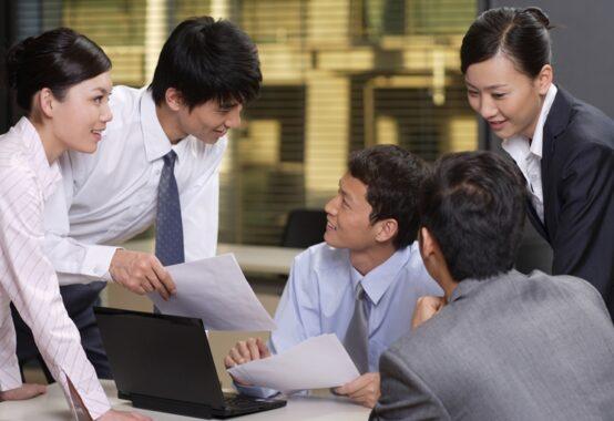 明るい顔で話し合う職場の人たち