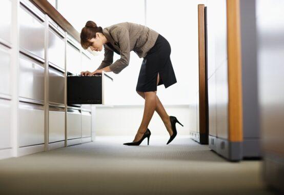 ファイルキャビネットから書類を探している女性