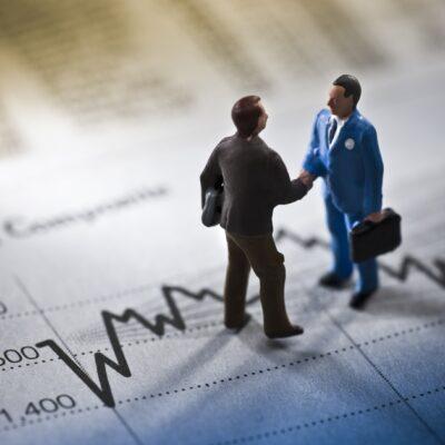 ビジネス資料の上で握手する二つのビジネスマン人形